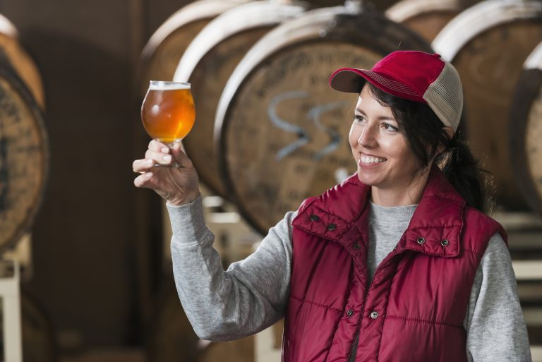 Woman working in a small brewery looking at a glass of beer she is holding.  The microbrewery manufactures craft beer.  The female worker or business owner is standing in front of wooden barrels.